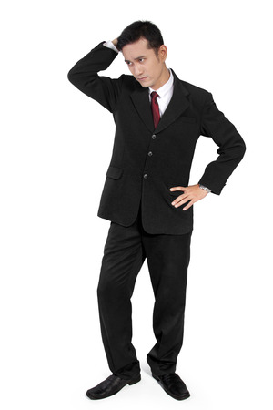 full shot: Full shot of young man in business suit with confused face standing awkwardly, isolated on white background
