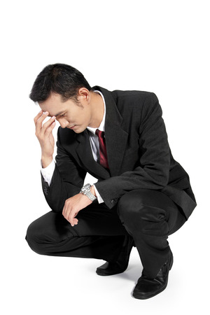 losing control: Young handsome businessman feeling upset, kneel down and holding his forehead, full body isolated on white background