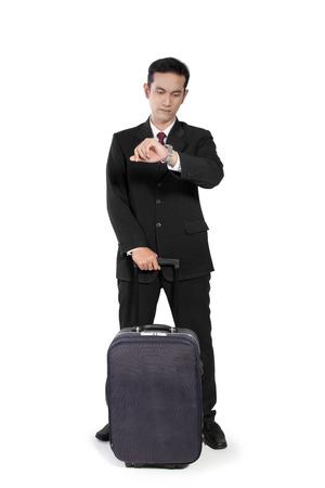 full body shot: Hombre de negocios asi�tico joven, de pie con bolsa de viaje y mirando su reloj, tiro de cuerpo completo, aislado en fondo blanco