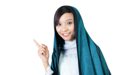 pointing finger up: Close up of smiling Asian muslim girl pointing finger up, isolated on white background