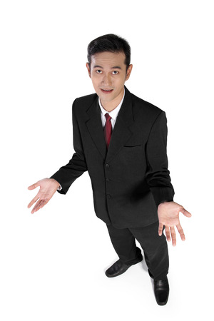 High angle full shot of young Asian businessman looking at camera with quizzical expression, isolated on white background
