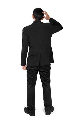 Back shot of clueless man in business suit scratching his head, full body isolated on white background