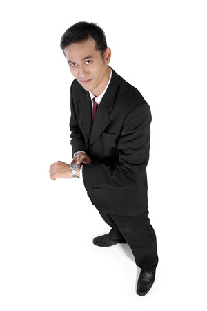 High angle full shot of attractive Asian businessman looking at camera and pointing at his wristwatch, isolated on white background Stock Photo