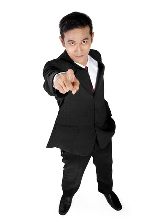 looking  up: High angle full shot of optimistic Asian businessman pointing one finger at camera, isolated on white background Stock Photo