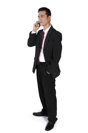 full body shot: Hombre de negocios asi�tico atractivo de pie con una mano en el bolsillo, buscando al mismo tiempo hacer llamadas de tel�fono, tiro de cuerpo completo, aislado en fondo blanco