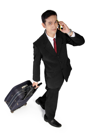 full shot: High angle full shot of young Asian businessman looking at camera while using mobile phone and pulling a suitcase, isolated on white background
