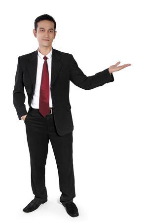 full body shot: Hombre de negocios asi�tico atractivo que se coloca y que presenta algo con la mano, tiro de cuerpo completo, aislado en blanco