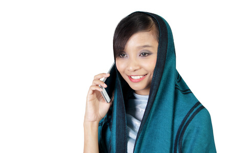 jilbab: Close up of smiling Asian muslim girl having conversation on smartphone, isolated on white background