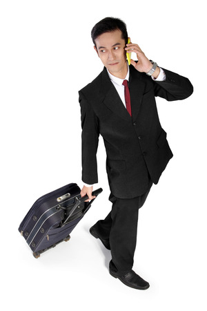 full shot: High angle full shot of attractive Asian businessman looking at the side while making phone call and pulling a suitcase, isolated on white background
