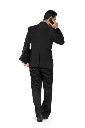 ウォーキングと全身白で隔離の携帯電話で話す若いアジア系のビジネスマンのバック ショット