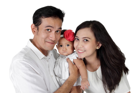 Happy Asian family portrait. Daddy and mommy with their little baby girl, isolated on white background