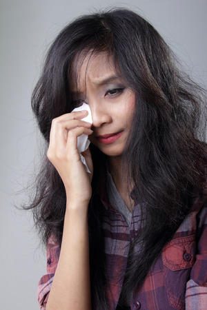adult crying: Portrait of young Asian woman crying, wipe her tears with tissue, on grey background