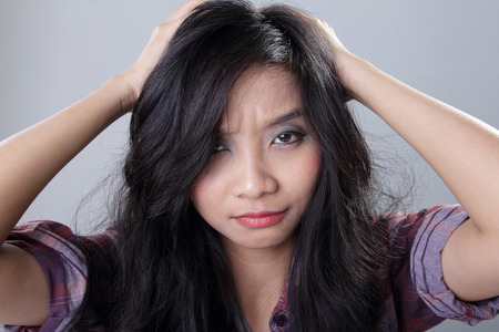 freak out: Face of frustrated woman pulling her hair with both hands while looking at camera, on grey background