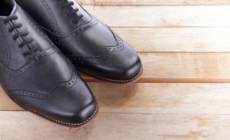 木製のテーブルの上に革の靴のペアのクローズ アップ
