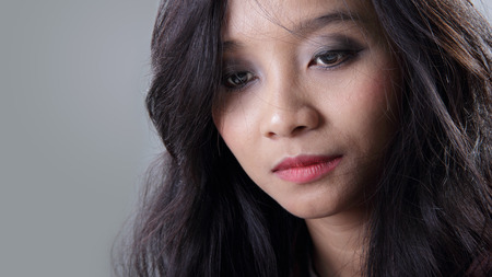 psychopath: Close up face of young Asian woman looking down with melancholic expression, on grey background
