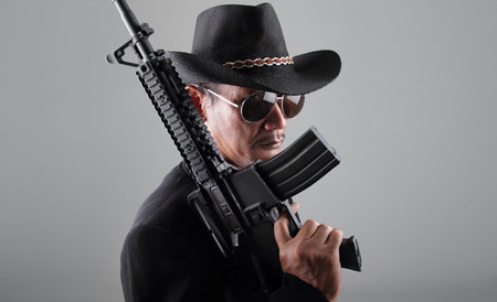 gangster background: An old gangster and his machine gun, over grey background