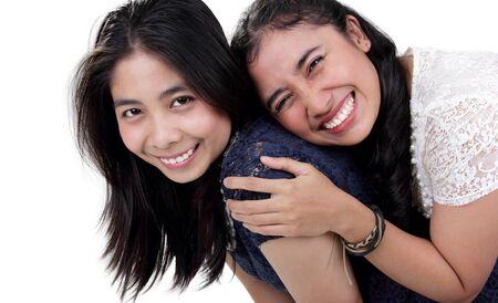 niñas sonriendo: Dos chicas asiáticas felices sonriendo mientras haciendo cuestas plantean, aislado en fondo blanco