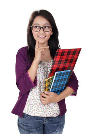 Friendly Asian teacher holding some books and looking to her side imaginatively, isolated on white background