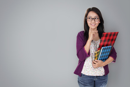 student library: Friendly Asian teacher holding some books and looking to copy space, isolated on grey background