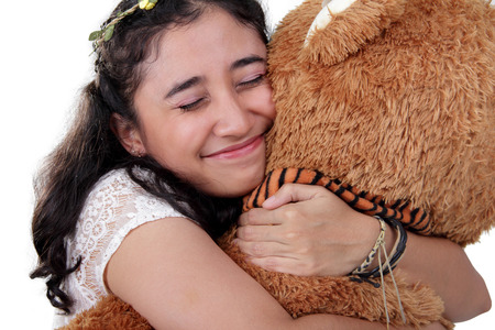 tightly: Happy sweet Asian girl hugging her big bear doll so tightly, over white background