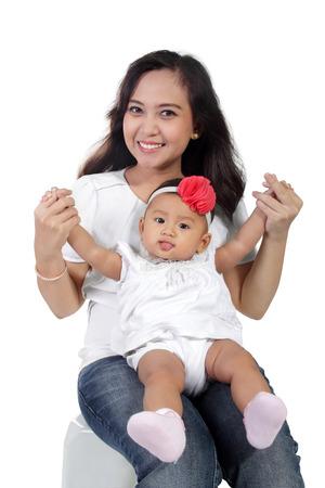 かわいい赤ちゃん女の子彼女の母親の周上に座っていると、彼女の舌を付着白背景に分離 写真素材