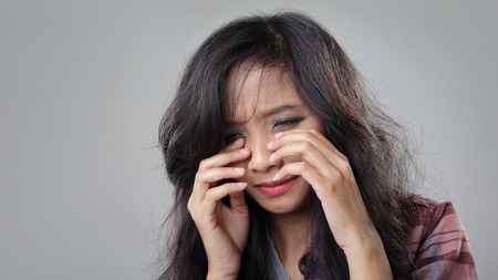 adult crying: Face of desperate young woman crying, on grey background