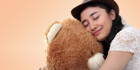 cream colored: Sweet Asian girl smiling while sleeping on top of teddy bear doll head, over cream colored background