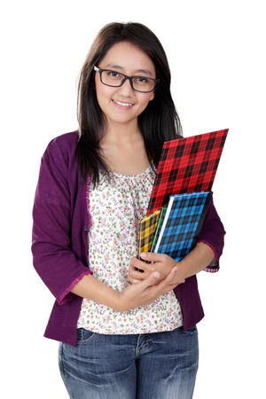 Friendly Asian teacher holding some books and smile to camera, isolated on white background Stock Photo