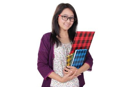 clase media: Mujer bibliotecario asiática cómoda posan con algunos libros y sonríe a la cámara, aislado en fondo blanco