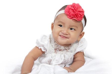 Portret van schattige lachende baby kruipen in bed, op een witte achtergrond Stockfoto