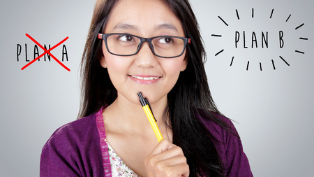 beautiful face: Close up face of optimistic Asian woman thinking of Plan B, looking up at hand written style text over grey background Stock Photo