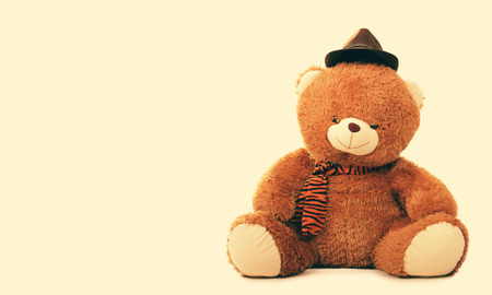 furry stuff: Classic style portrait of fashionable teddy bear doll, over cream colored background with copy space Stock Photo