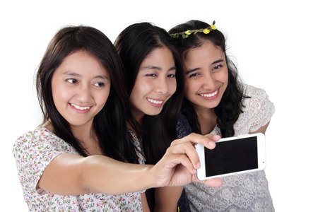 narcissism: Three cheerful Asian girls taking a self shot picture with smartphone, isolated on white background Stock Photo