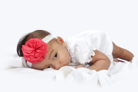 tired face: Tired baby lying in bed with sleepy eye, isolated on white background Stock Photo