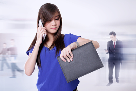 hectic: Conceptual image of business people lifestyle. Young Asian businesswoman looking at her wrist watch while talking on phone, and some businessman doing activities on background Stock Photo