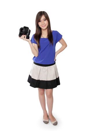 brings: Pretty teenage girl with beautiful smile brings a black camera with her right hand while standing, isolated on white background