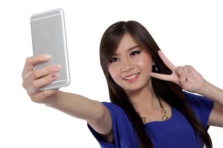 signo de paz: Muchacha asiática linda que sonreír y hacer signo de la victoria, mientras que tomar una foto disparo auto con su cámara frontal del smartphone, aislado en fondo blanco