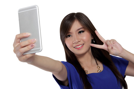Cute Asian girl smile and make victory sign while take a self shot photo with her smartphone front camera, isolated on white background Archivio Fotografico