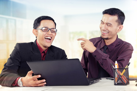 fun at work: Two young Asian business partners laughing on a discussion at their workplace Stock Photo