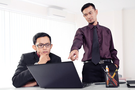 business concern: Attractive Asian office worker showing something to his co-worker on a laptop at their office workplace