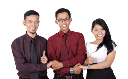 joining hands: Three cheerful Asian business partners joining hands and giving thumbs up at camera, isolated on white background Stock Photo