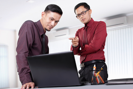 Two attractive Asian office workers discussing something on a laptop at their office workplace