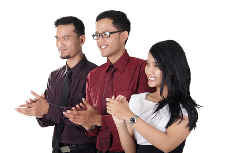 Side profiles of three happy Asian businesspeople clapping hands together, isolated on white background