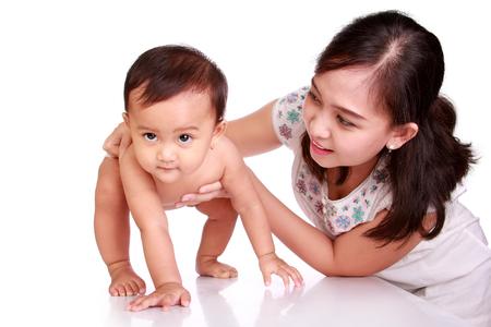 歩くことを学んで、彼女の母によって導かれて、白い背景で隔離のかわいいアジアの赤ちゃん 写真素材
