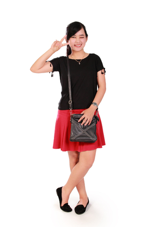 liberated: Stylish Asian girl standing and making a cute cheerful pose to camera, full body portrait isolated on white background