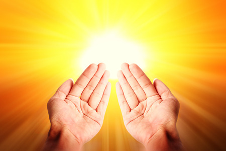 religious life: Islamic religious image. Closeup of open hands pray over yellow bright light background