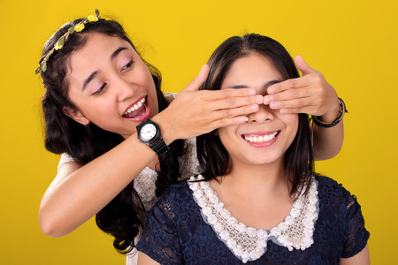 guessing: Two happy Asian female friends play guessing game. One girl covering her friends eyes, over yellow background