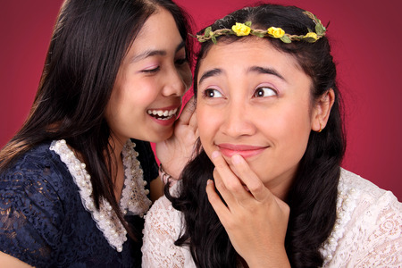 hearsay: Two lovely Asian girls gossiping. One girl with funny face expression while hearing her friend says something on her ear