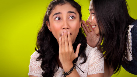 hearsay: Gossip  rumor  hearsay. Surprised face of Asian girl when her friend tells a shocking news