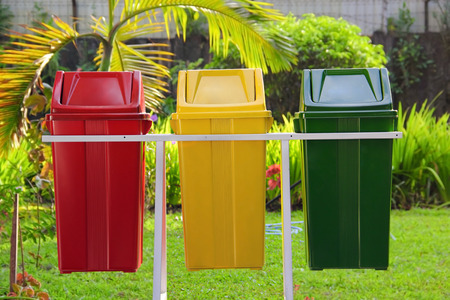 degradable: Three colorful trash cans in the park Stock Photo
